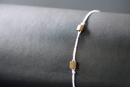 Bracelet white with two brass beads