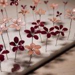 Viele Nagellackblümchen in Rosanuancen aus Draht und Nagellack