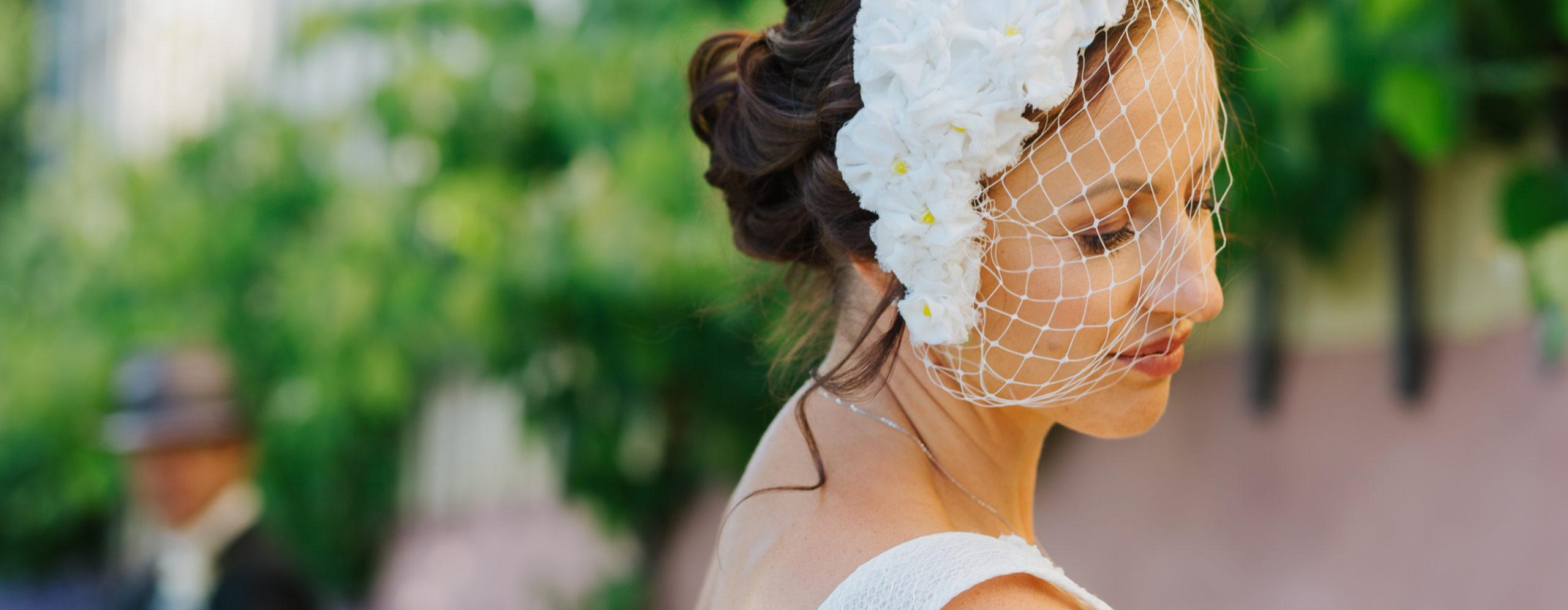 Braut mit Fascinator mit Vintageschleier